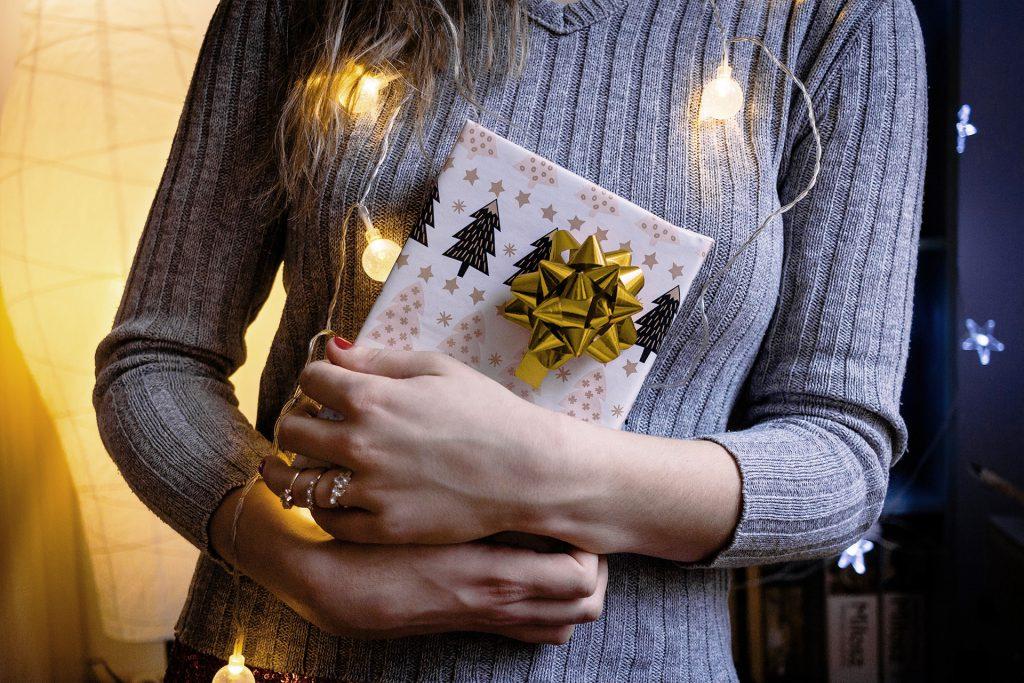 Frau hält Geschenk | Titelbild Hallo Glück | Gegen Stress beim Geschenke kaufen
