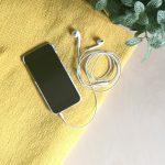 Hallo Glück | Smartphone mit Playlist und Kopfhörern auf Tisch