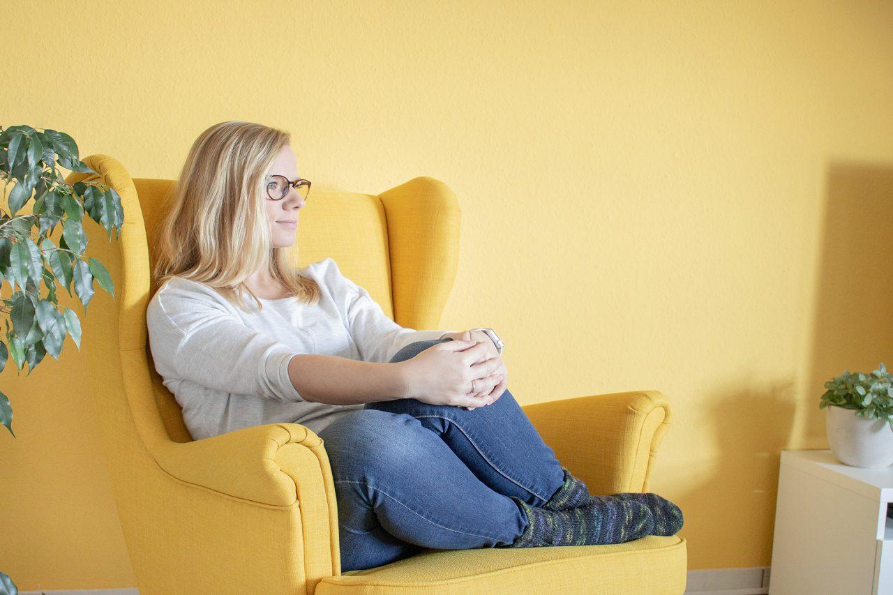 Sandra sitzt nachdenklich auf einem Sessel